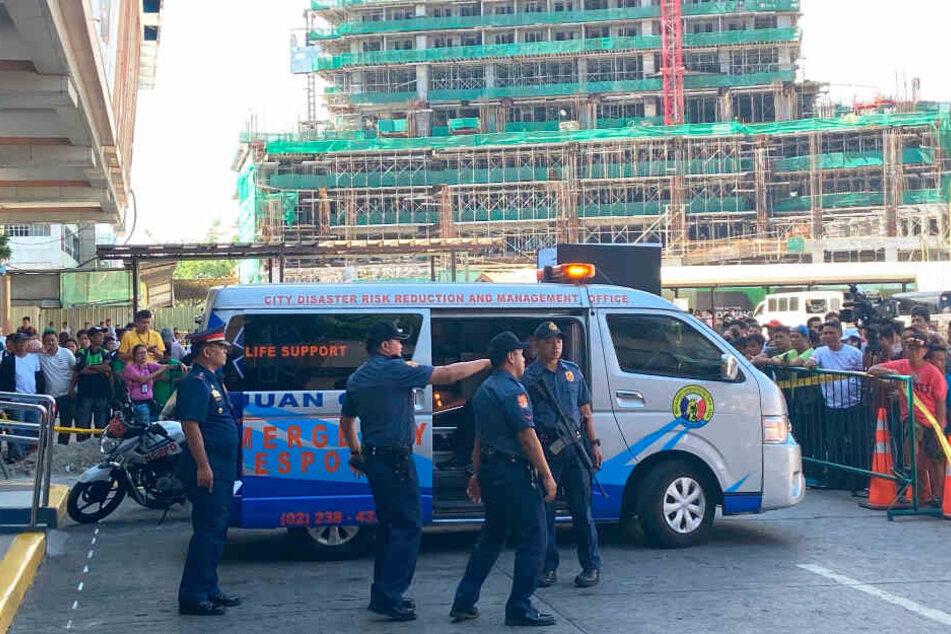 """Sicherheitsbeamte stehen vor dem Einkaufszentrum """"V-Mall"""", dahinter haben sich hinter einem Absperrband zahlreiche Menschen versammelt."""