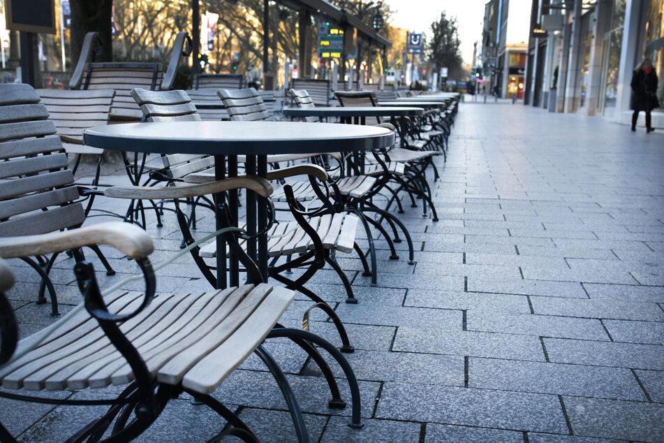 Eine Frau geht am Morgen an leeren Stühlen und Tischen auf der Königsallee vorbei.