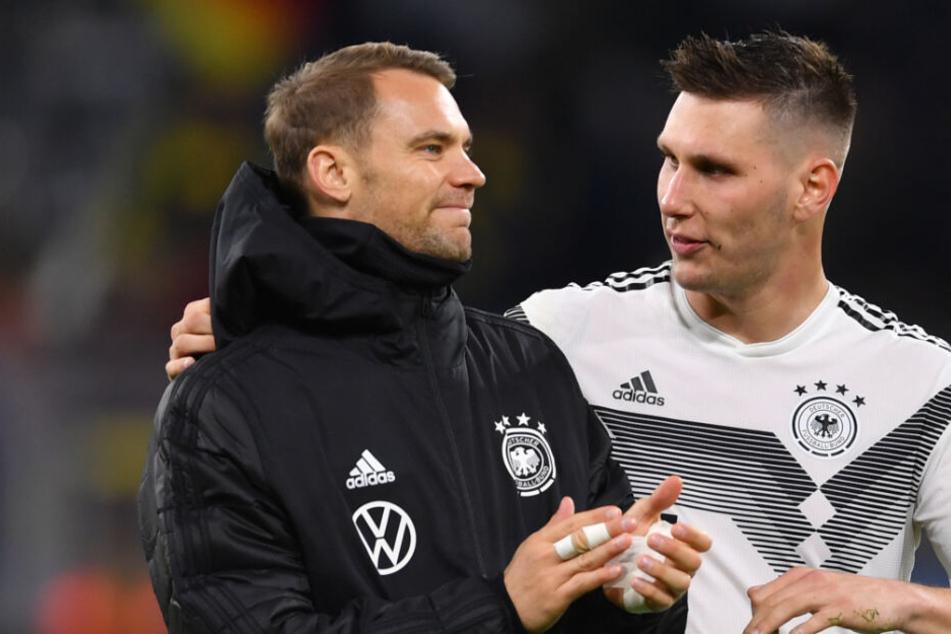 Niklas Süle (r) und Torhüter Manuel Neuer reden nach einem Länderspiel.