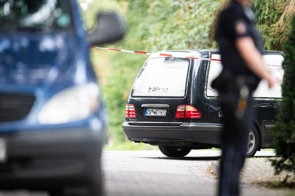 Ein Leichenwagen fährt am abgesperrten Tatort vor. (Symbolbild)