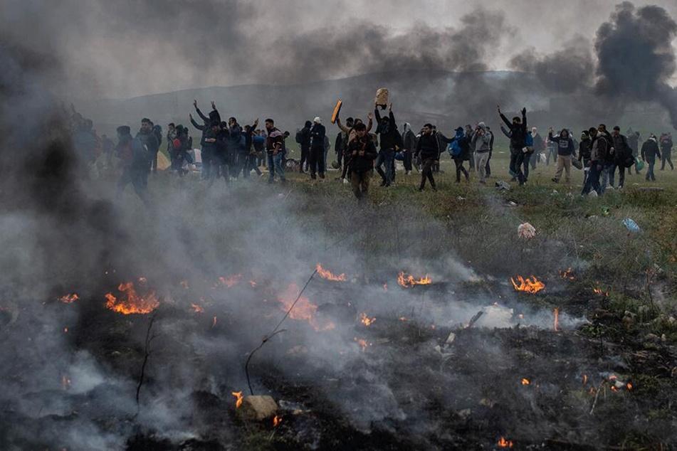 Protestierende Migranten stehen inmitten von Rauchwolken bei Zusammenstößen mit der Polizei nahe einem Flüchtlingslager im Dorf Diavata in der Nähe von Thessaloniki.