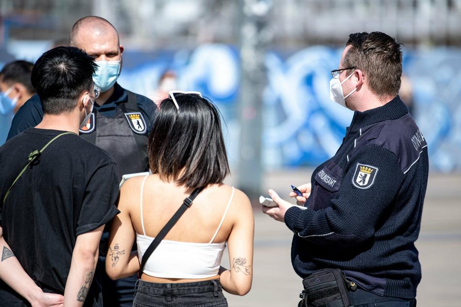 Mitarbeiter des Ordnungsamtes erheben ein Bußgeld von zwei Passanten.