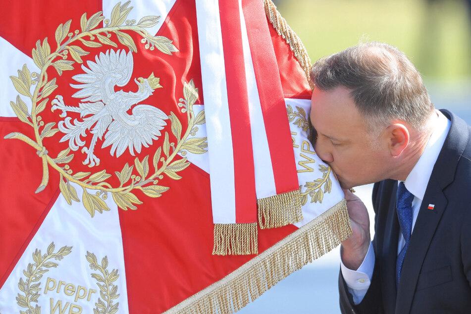 Andrzej Duda (48), wiedergewählter Präsident von Polen, küsst auf dem Pilsudski-Platz in Warschau eine Flagge der polnischen Streitkräfte.