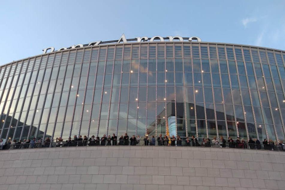 Konzertbesucher der Benz-Arena beobachten das Treiben und Gewusel vor der Halle.
