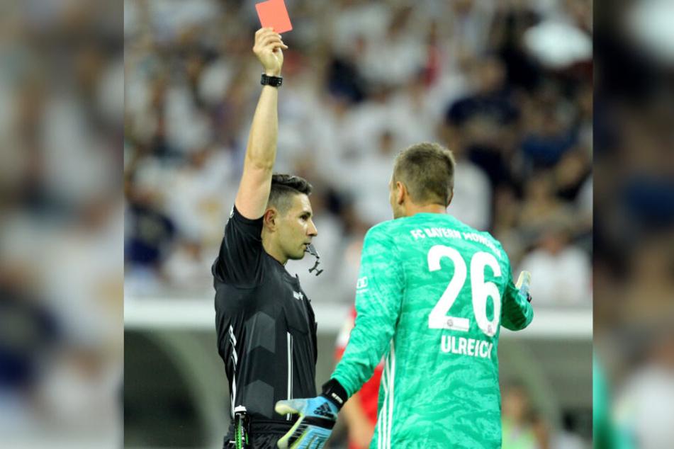Münchens Torhüter Sven Ulreich erhält von Schiedsrichter Ramy Touchan die Rote Karte.
