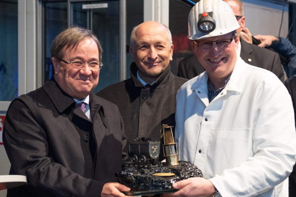 Armin Laschet (CDU) nimmt von einem Bergmann ein Stück Kohle als Geschenk im Empfang.