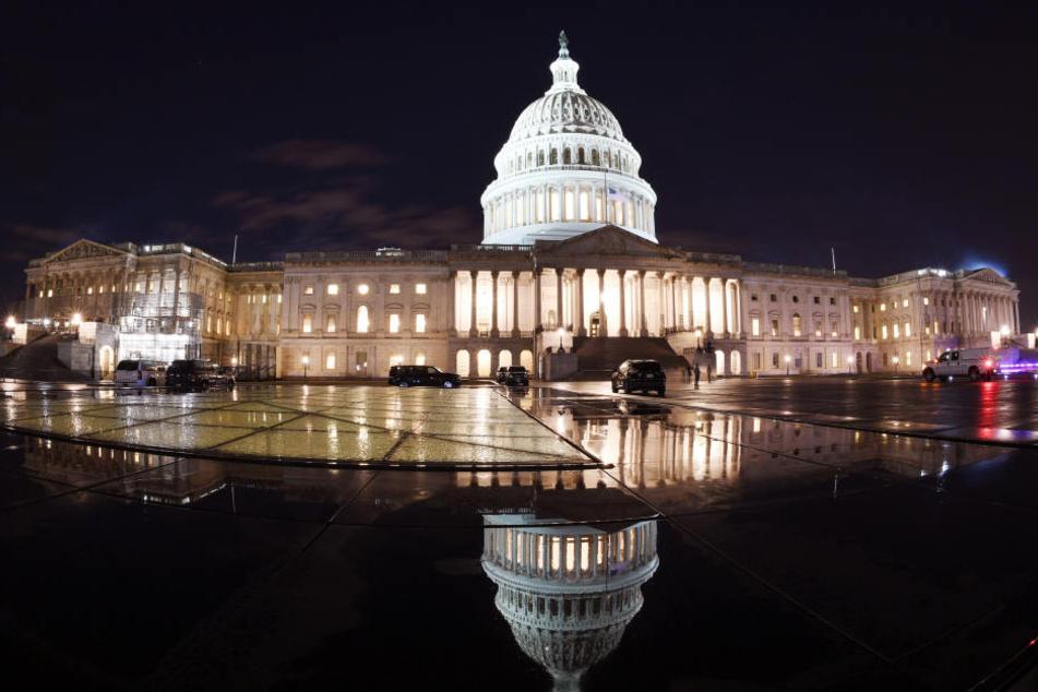 Das Kapitol in Washington spiegelt sich in der Nacht. In den USA sind kurz vor Weihnachten die Regierungsgeschäfte teilweise lahmgelegt.