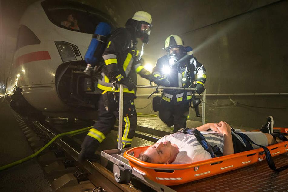 """Feuerwehrmänner schieben einen """"Verletzten"""" auf einem speziellen Schienenwagen aus dem Tunnel."""