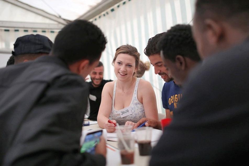 Eine ehrenamtliche Helferin mit Flüchtlingen beim Deutschkurs.