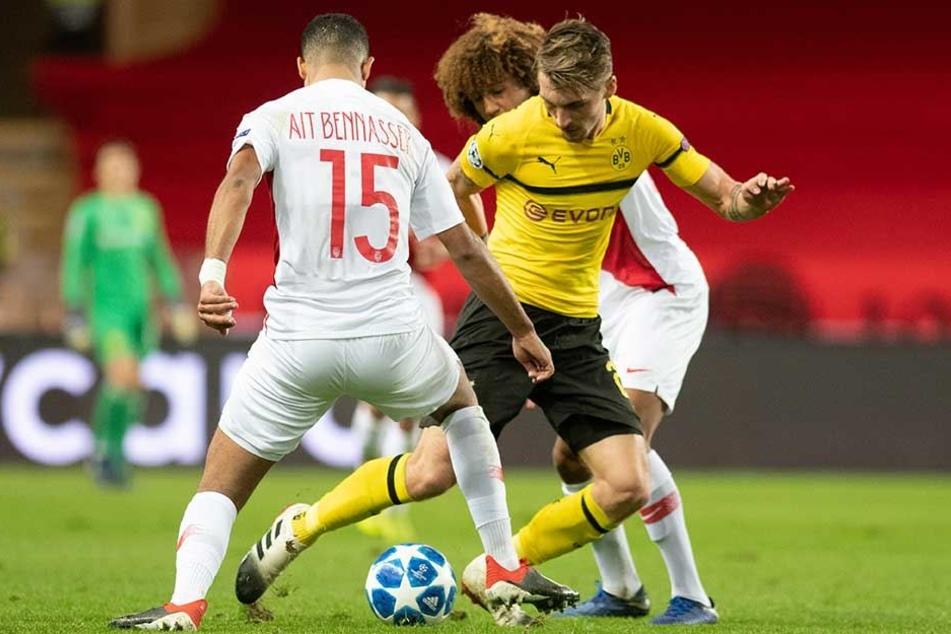 Maximilian Philipp (M) und Youssef Ait Bennasser (l) und Han-Noah Massengo von Monaco kämpfen um den Ball.