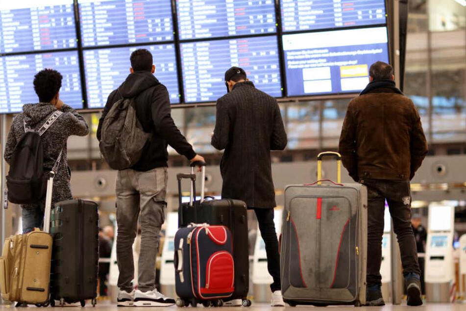 Reisende gucken am Flughafen Hamburg, ob ihr Flug pünktlich ist. (Symbolbild)