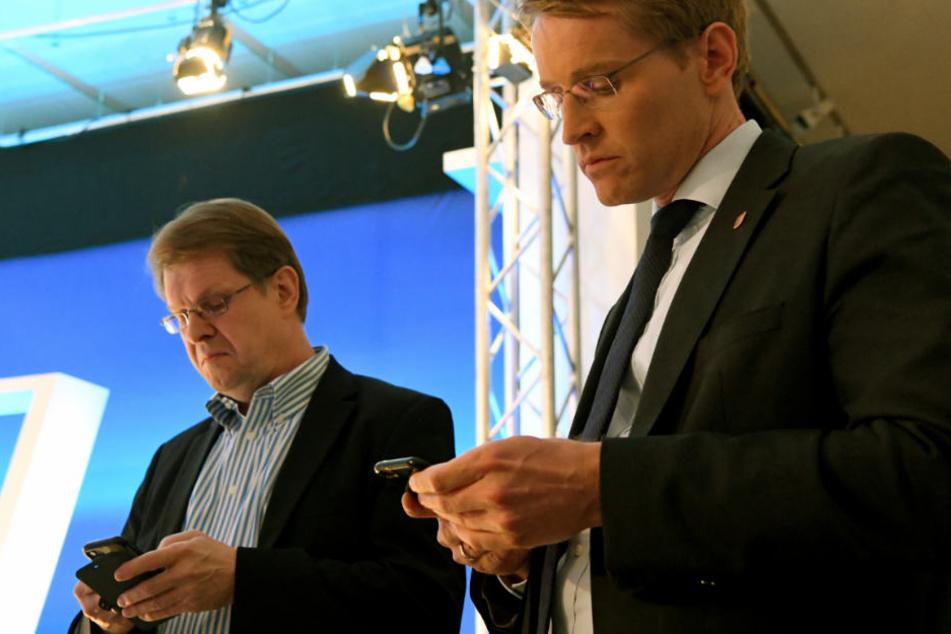 Ralf Stegner (SPD) und Daniel Günther (CDU) verfolgen die Wahl auf ihren Smartphones.