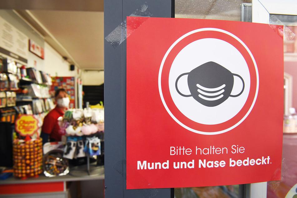 """Ein Schild mit dem Schriftzug """"Bitte halten Sie Mund und Nase bedeckt"""" hängt an einem Geschäft in der Ladenstraße von Stralsund."""