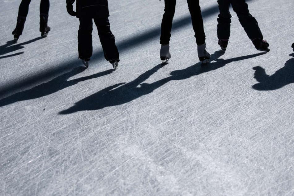Einige Schlittschuhfahrer gleiten über das Eis in Frankfurt.