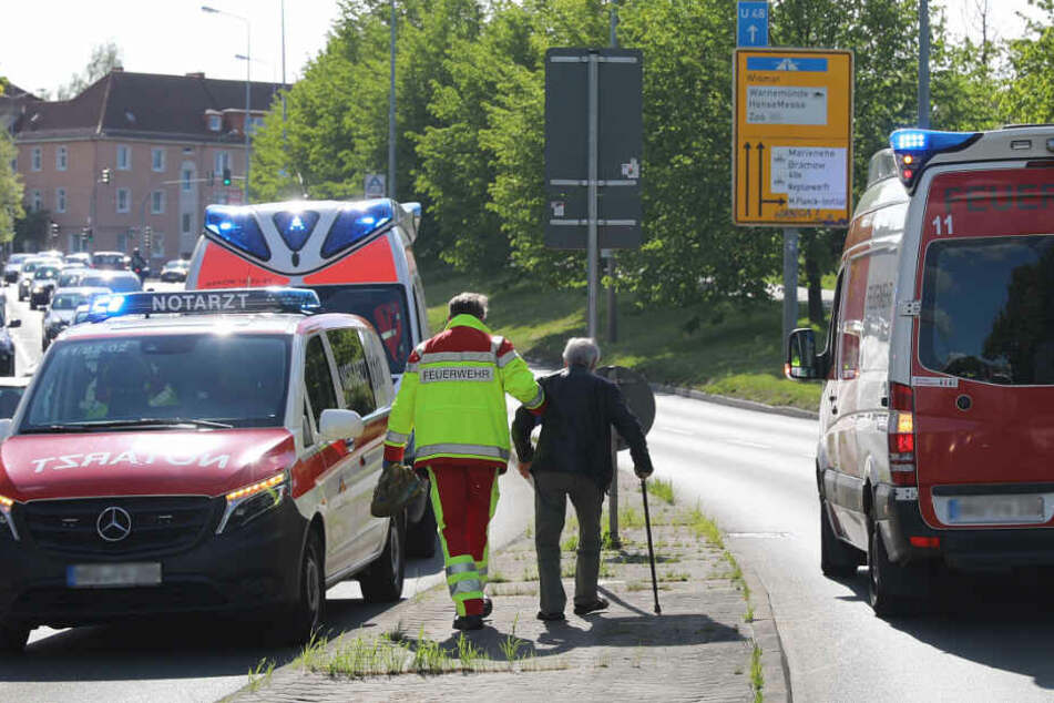 Ein Beamter der Feuerwehr muss den Unfallfahrer, einen 82-jährgen Senior, der am Stock geht, nach dem Unfall stützen.