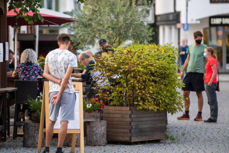 Ein Mann schaut sich eine Speisekarte einer Bar in Garmisch Partenkirchen an.