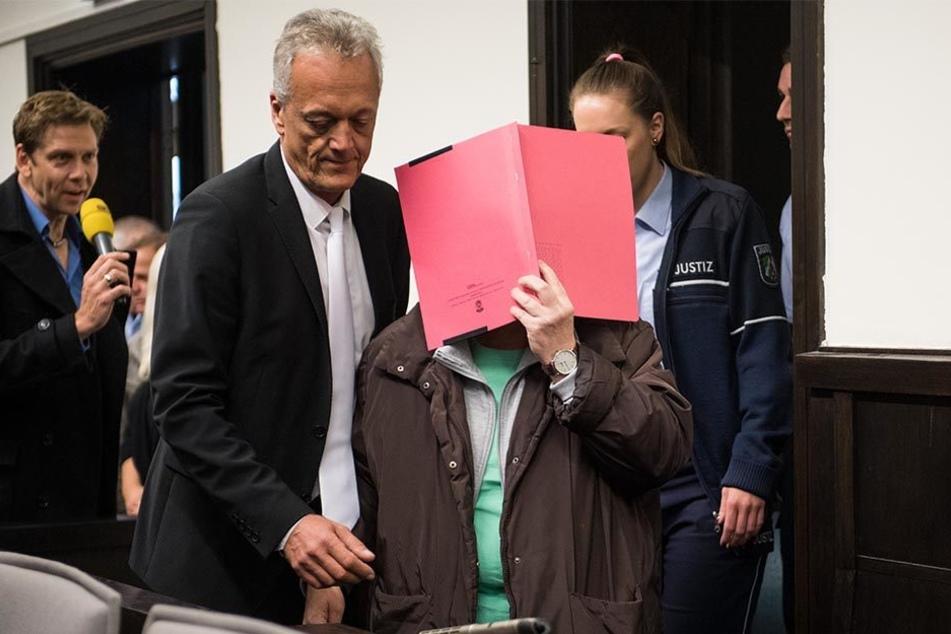 Angelika W. hielt sich bei Prozessbeginn eine rote Akte vor das Gesicht. Sie möchte nicht erkannt werden.