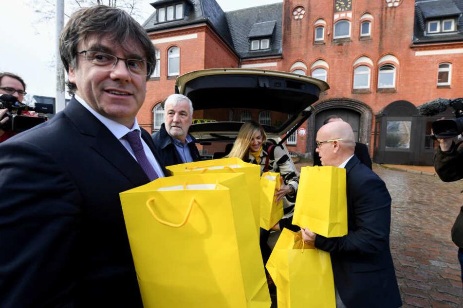 Der katalanischer Separatistenführer Carles Puigdemont hält vor der JVA gelbe Tüten in der Hand. Er brachte 100 Bücher katalanischer Autoren in deutscher Übersetzung für die Gefängnisbibliothek mit.