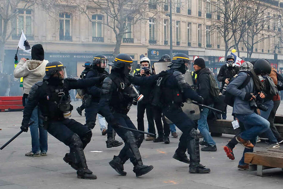 Ein Fotograf bringt sich während der Demos in Sicherheit.