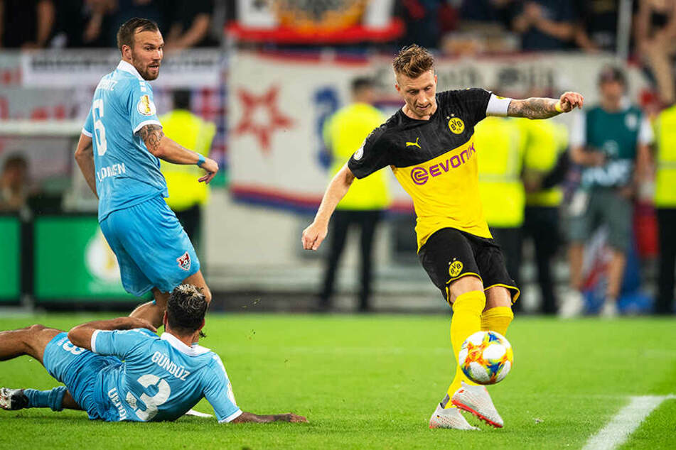 BVB-Kapitän Marco Reus trifft zum 1:0 für Dortmund. Kevin Großkreutz (oben-links) und Selim Gündüz (unten-links) können nicht mehr eingreifen.