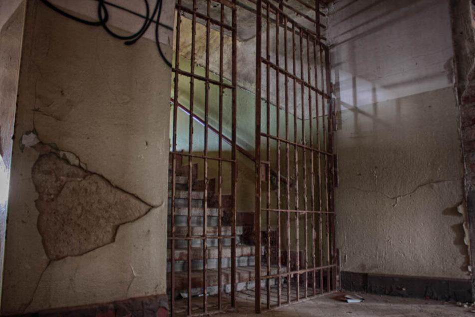 Eine Treppe führt auf den Dachboden, davor eine massive Gittertür.