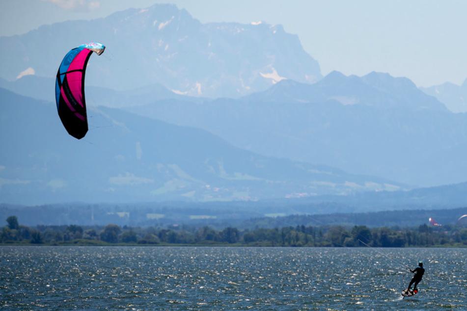 in Kitesurfer fährt über den Ammersee. Seit Mittwoch gibt es auch neue Regeln für die Freizeitgestaltung in Bayern.