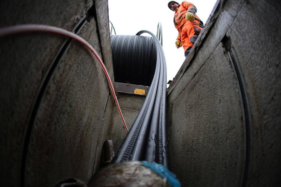 Ein Arbeiter verlegt Glasfaserkabel. Viele Kreise und Kommunen nehmen  Millionen in die Hand, um den Breitbandausbau voranzutreiben