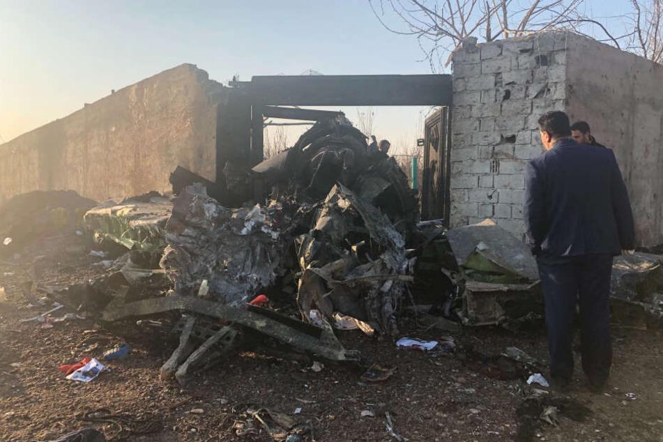 Männer stehen neben Trümmern nach einem Flugzeugabsturz am Rande von Teheran.