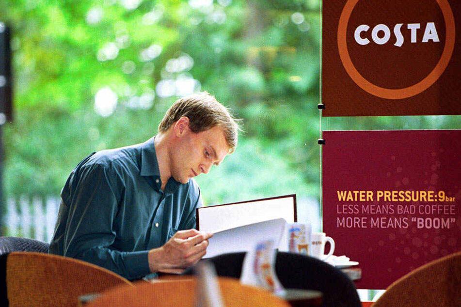 Ein Mann verbringt seine Kaffeepause im Kaffeehaus Costa.