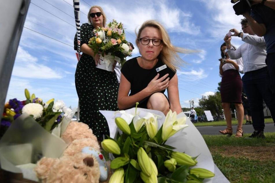 Eine Stadträtin legt am Unglücksort Blumen nieder.