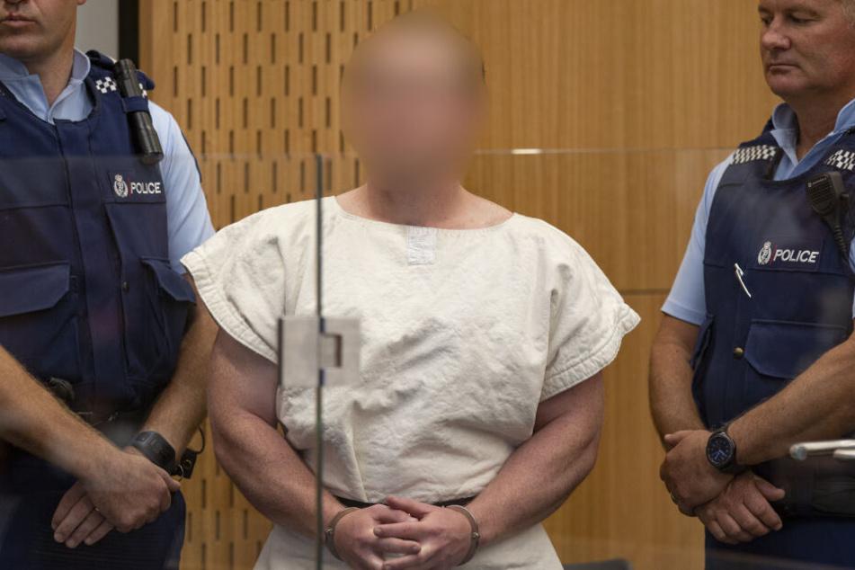 Der mutmaßliche Täter steht mit Handschellen vor einer Anhörung im Bezirksgericht.