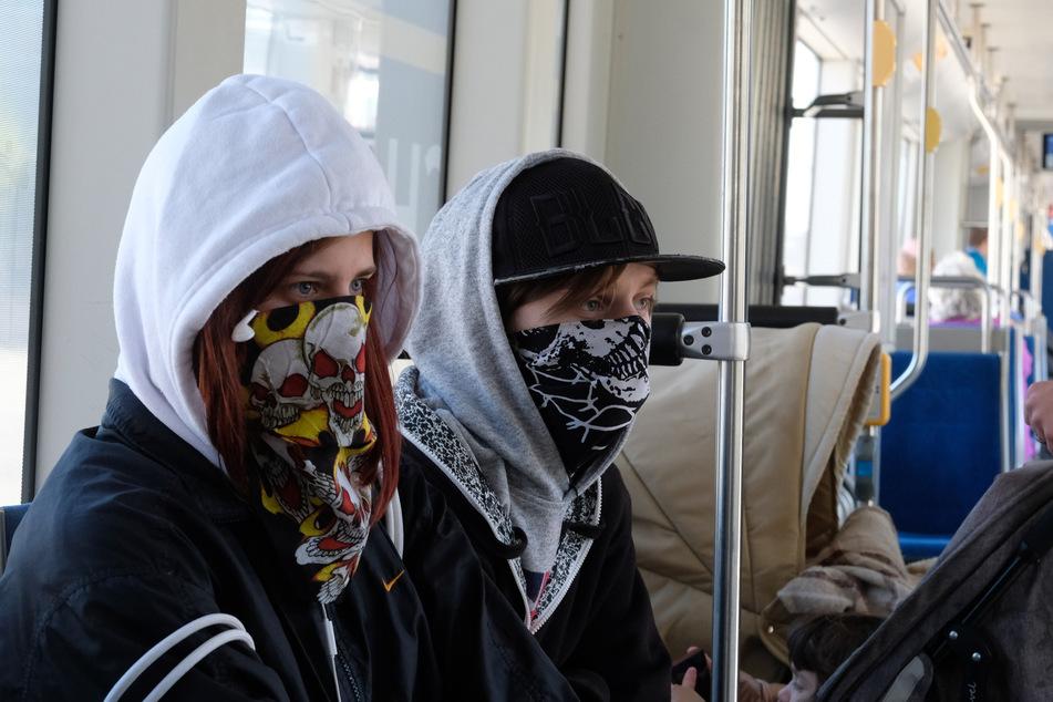 Fahrgäste einer Straßenbahn tragen Bandanas als Mundschutz.
