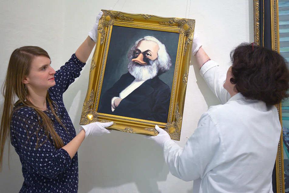 """Museumspädagogin Marleen Dietz (27, l.) und Museologin Birgit Mix (52) hängen """"Karl Duck"""" - angelehnt an Karl Marx - auf."""