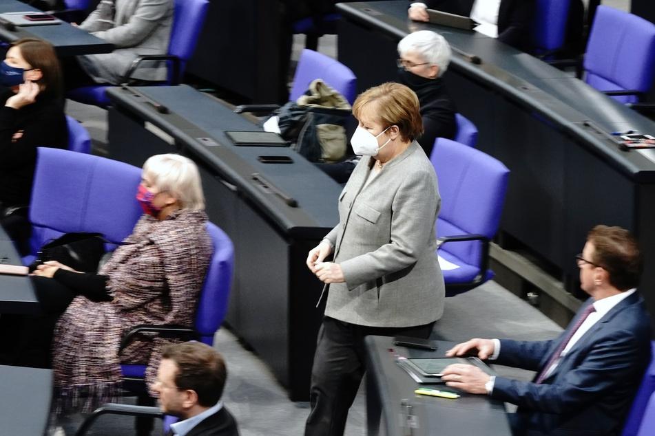 Bundeskanzlerin Angela Merkel (CDU) geht mit Mund-Nasenbedeckung während der Debatte vor der Verabschiedung der Änderung des Infektionsschutzgesetzes , dem Gesetzes zum Schutz der Bevölkerung bei einer epidemischen Lage von nationaler Tragweite, durch den Plenarsaal.