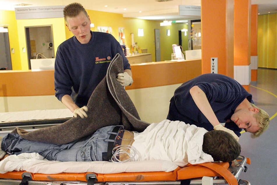 """Zwei Rettungssanitäter kümmern sich vor der Notaufnahme des Kinderkrankenhauses in Hannover einen jugendlichen """"Komasäufer""""."""
