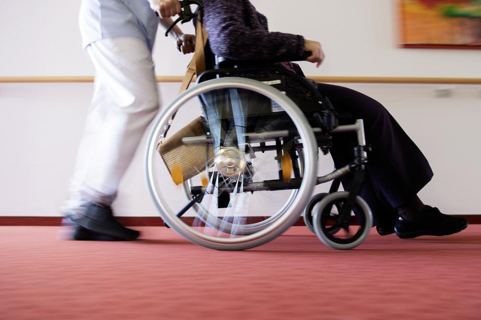 Ein Pfleger schiebt eine Bewohnerin eines Pflegeheims in einem Rollstuhl über den Flur. Zum internationalen Tag der Pflege am 12. Mai demonstrieren Pflegende mit vielfältigen Aktionen für bessere Arbeitsbedingungen. (Symbolbild)