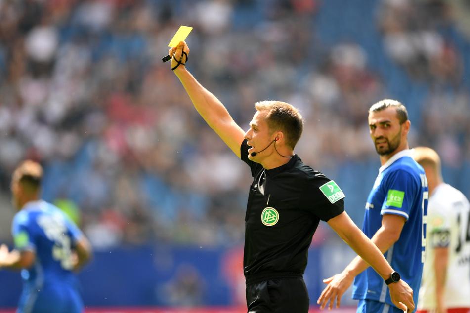 Schiedsrichter Robert Hartmann zeigt die Gelbe Karte.