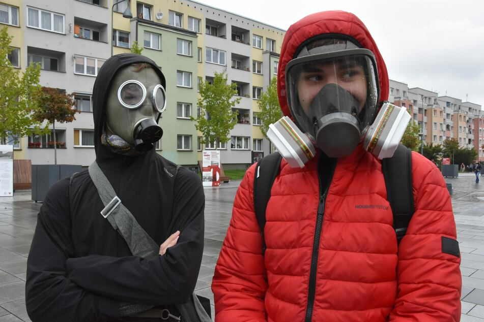 Zwei Jugendliche aus Polen tragen eine Gas- und eine Atemschutzmaske, im deutschen Nachbarland gibt es aktuell mehr Corona-Infektionen als je zuvor.