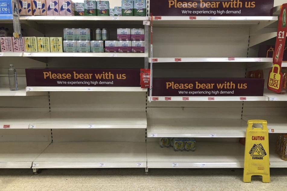 Blick auf leere Regale und Schilder im Gang für alkoholfreie Getränke in einer Sainsbury's-Filiale.