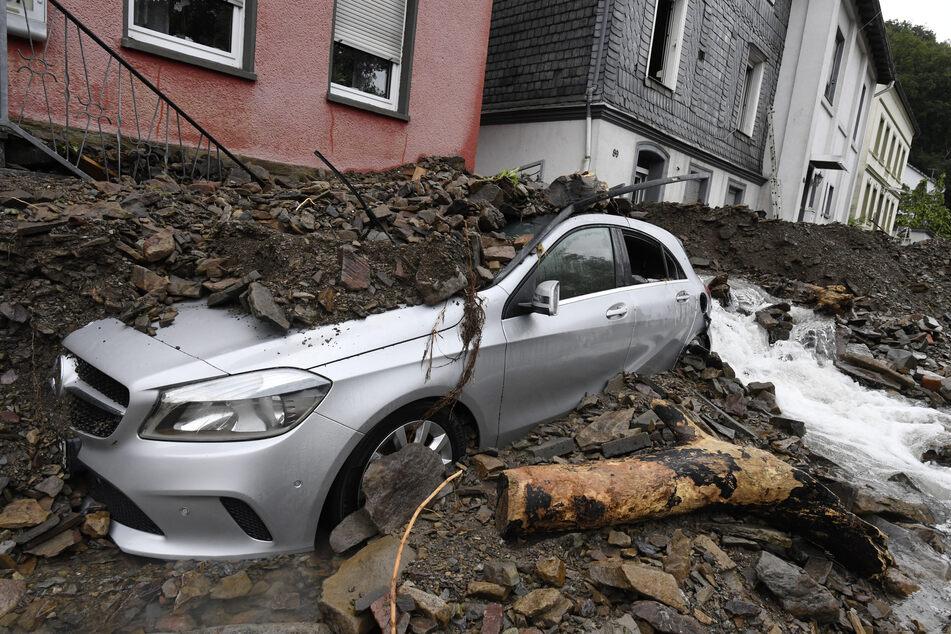 Ein Auto ist in Hagen von Schutt bedeckt, den die Überflutung des Nahmerbach am Vorabend mit sich gebracht hatte.