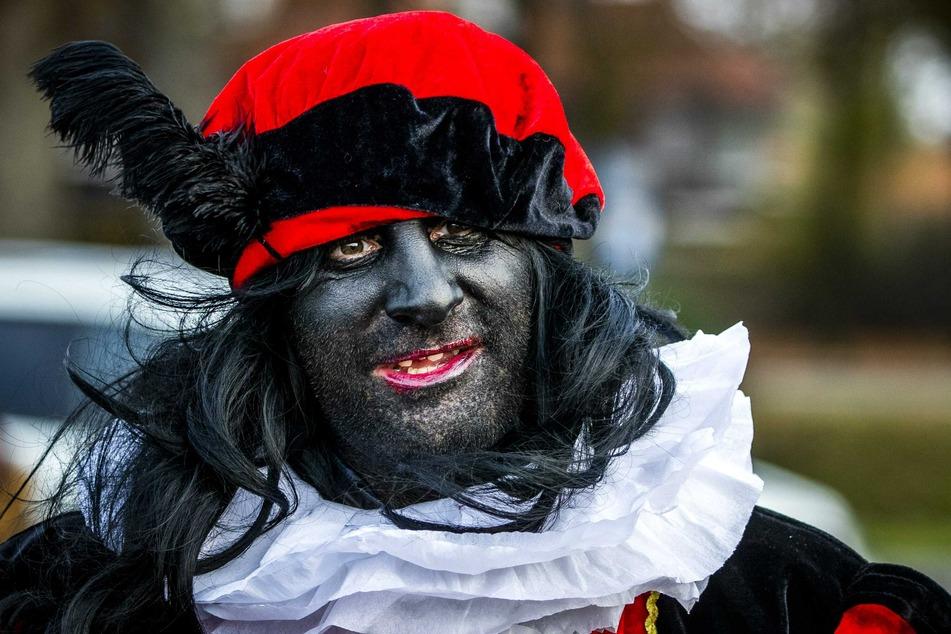 """Ein Demonstrant, der als der """"Zwarte Piet"""" verkleidet ist, nimmt an einem Protest der Aktionsgruppe """"Kick Out Zwarte Piet"""" (KOZP) teil."""