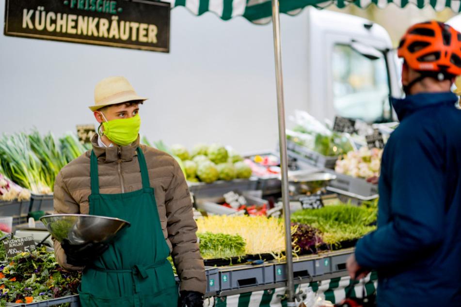 Ein Mitarbeiter bedient mit einem Mundschutz die Kunden auf dem Isemarkt.