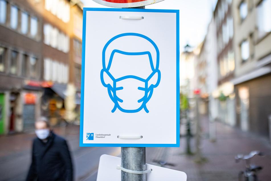 Düsseldorf: Ein Schild mit dem Symbol für Maskenpflicht ist an einem Straßenschild in der Innenstadt befestigt.