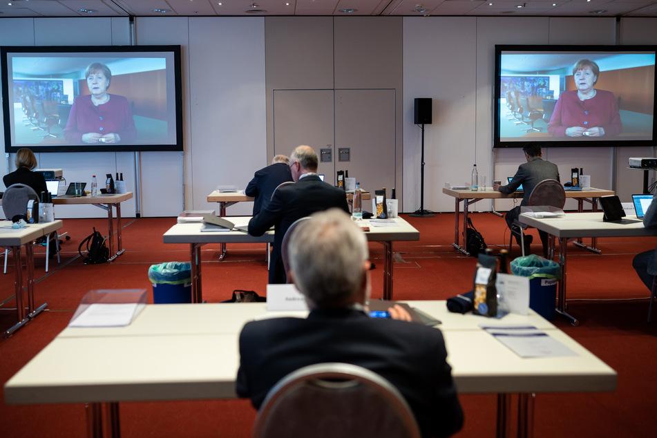 Teilnehmer des 124. Deutschen Ärztetages, der zum größten Teil rein digital stattfindet, verfolgen das Grußwort von Bundeskanzlerin Angela Merkel.