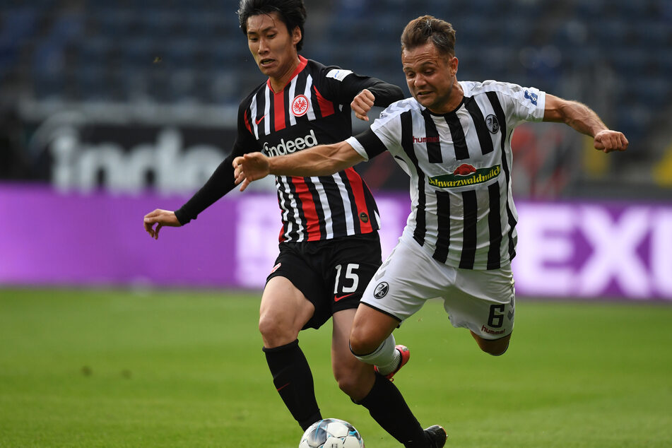 Daichi Kamada (l.) von Eintracht Frankfurt versucht den Ball gegen Freiburgs Amir Abrashi zu behaupten.