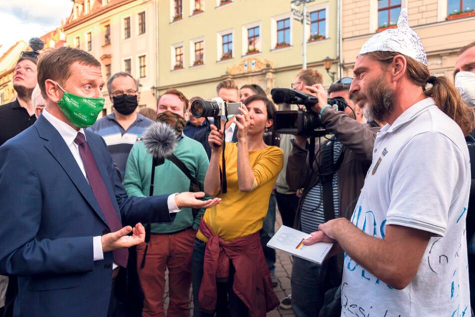"""Auch mit sprichwörtlichen """"Aluthut-Trägern"""", wie hier in Pirna, redet der Regierungs-Chef."""
