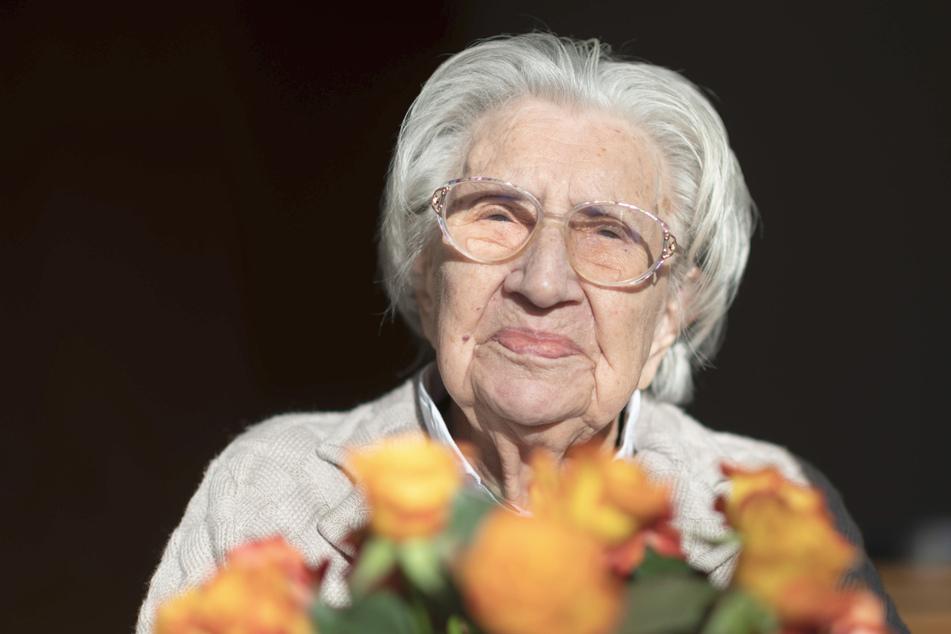 Mina Hehn hat an ihrem 108. Geburtstag in ihrem Terasseneingang in einem Pflegeheim einen Blumenstrauß auf dem Schoß.
