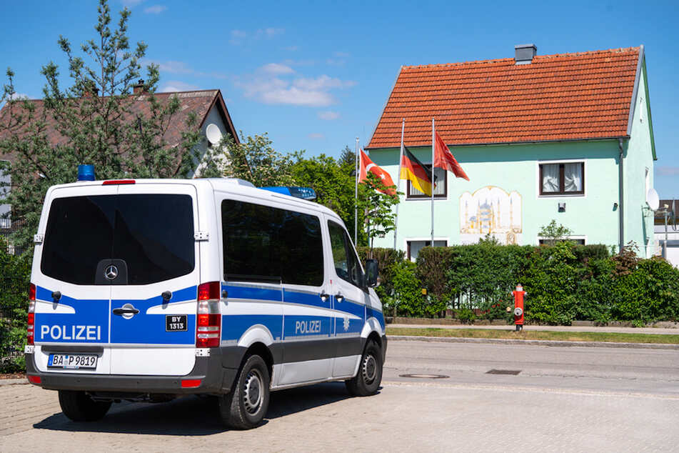 Polizisten beobachten aus einem Polizeifahrzeug das Gebäude des Türkisch Islamischen Kultur Vereins DITIB.