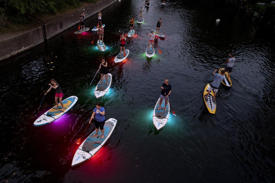 Teilnehmer einer Ausflugsgruppe fahren mit leuchtenden LED-SUPs in den Abendstunden über einen Alsterfleet.