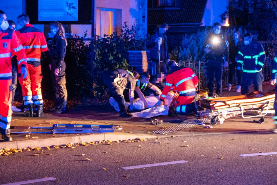 Rettungskräfte versorgen die Verletzten auf dem Gehweg.